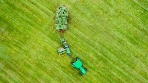 Drone Photograph of birds eye view of farm tractor with hay bails in New Jersey