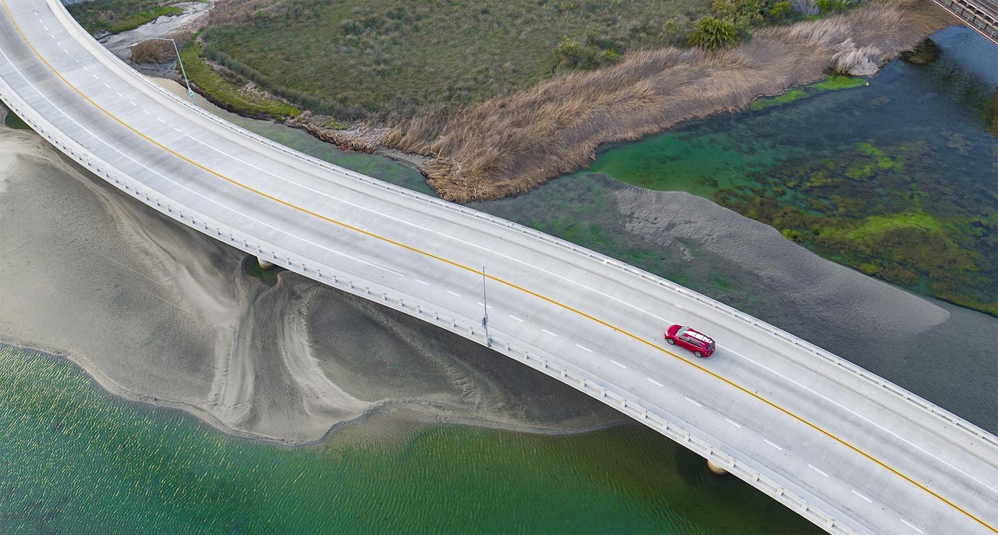 Photograph of birds eye view of SUV with surf board on roof crossing marsh bridge taken with a drone