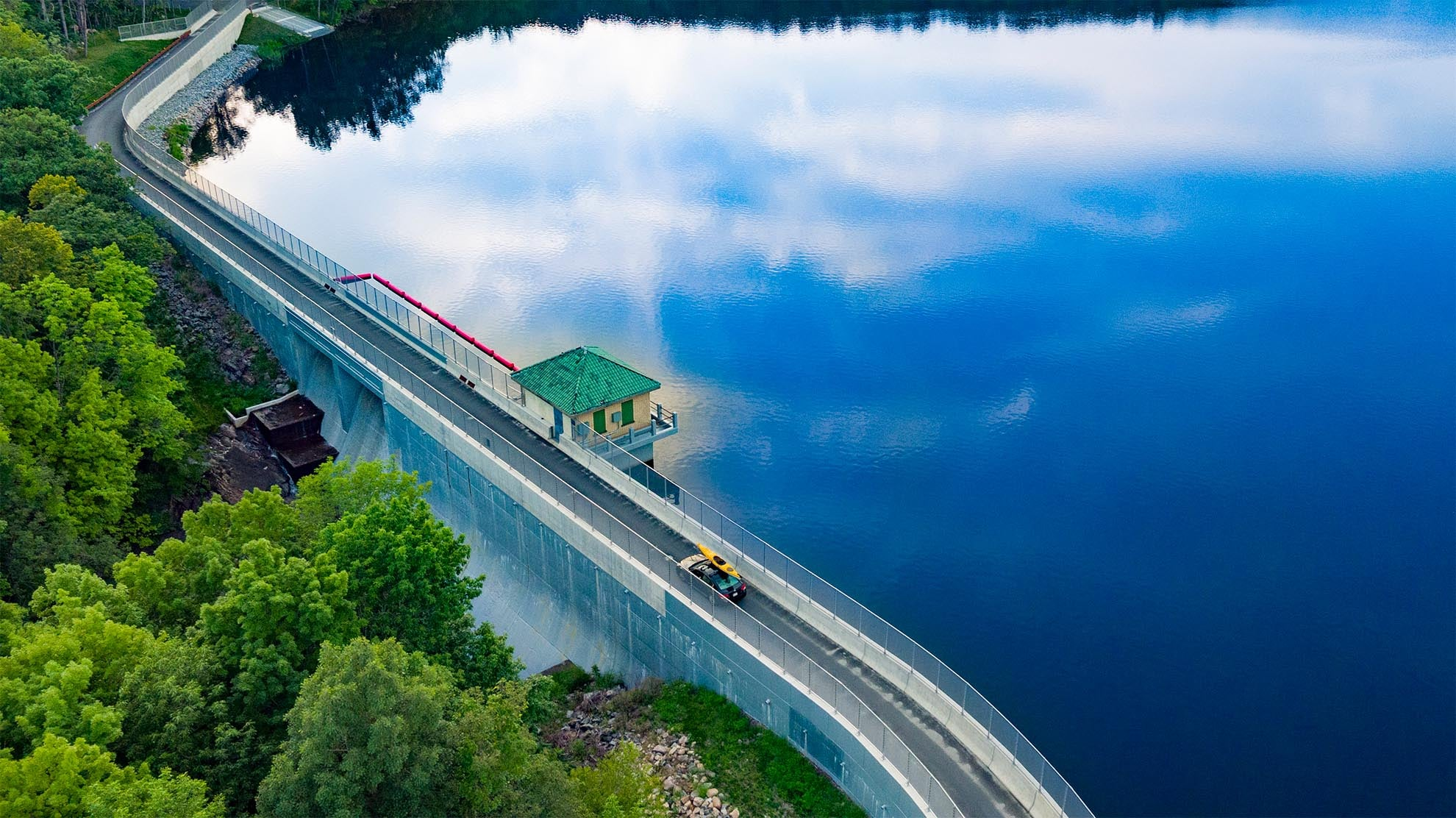 Drone Photograph of car with yellow kayak on roof crossing the Split Rock Dam