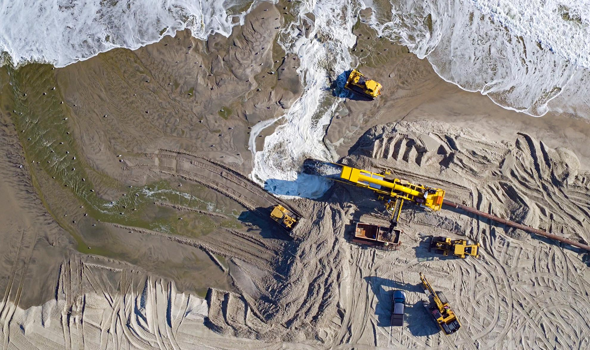 Drone Photograph of birds eye view of Excavating equipment Rebuilding Beach on the New Jersey Shore
