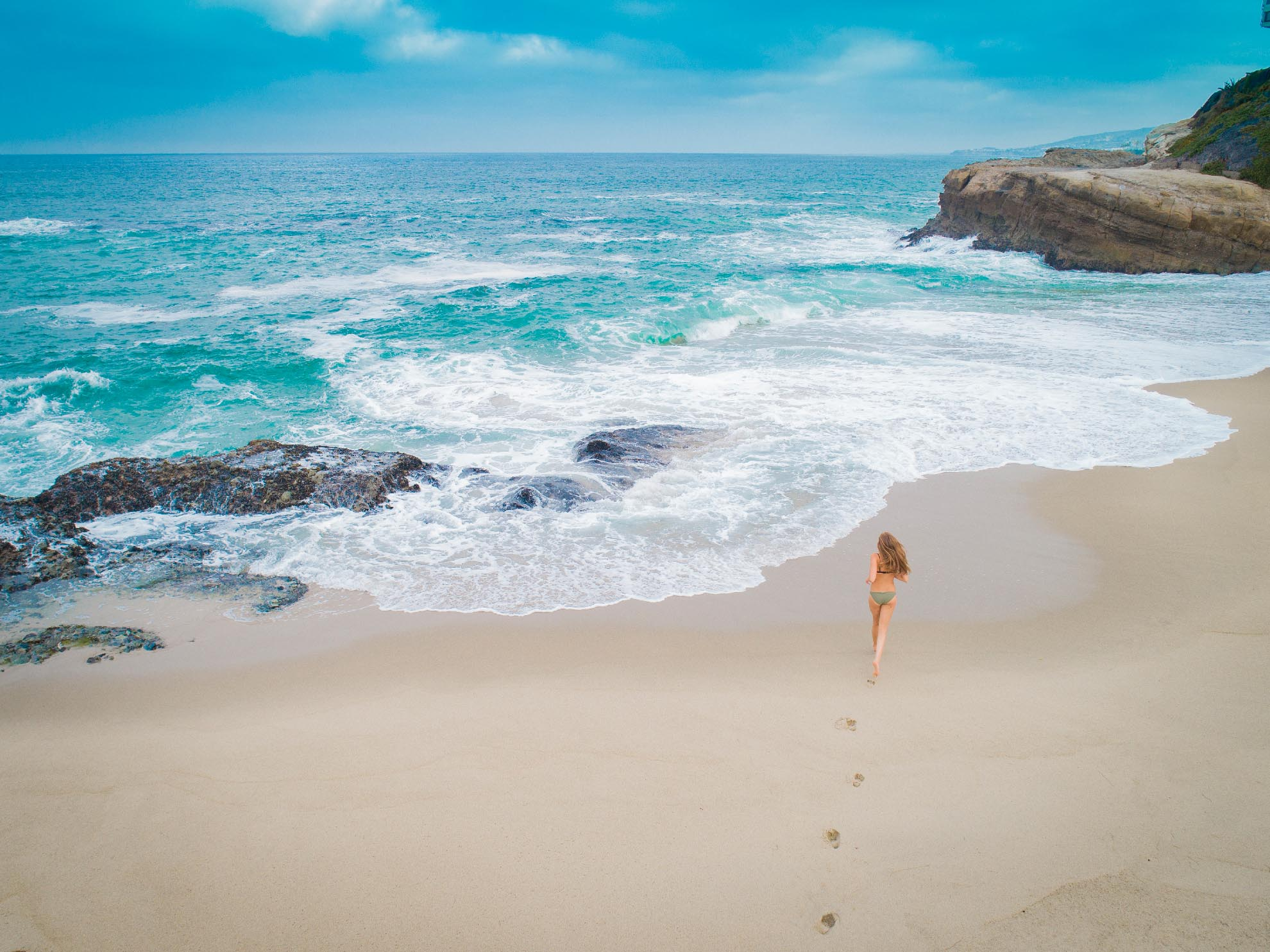 Drone Photgraph of young woman running on table rock beach California