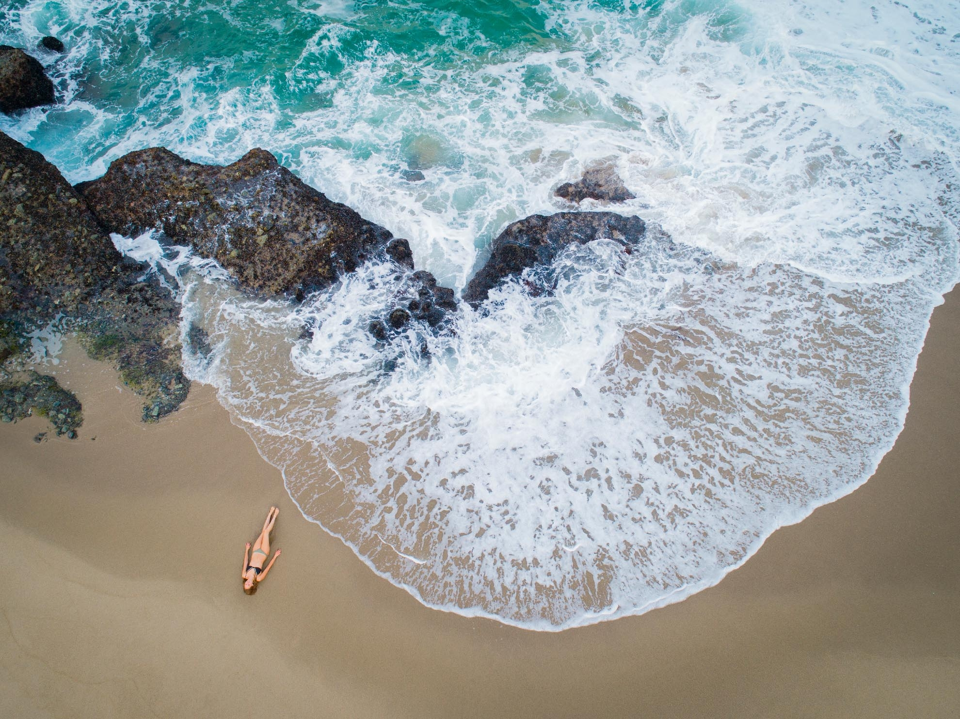 Drone Photograph of birds eye view of woman lying on Table Rock beach California in a bikini
