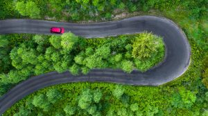 Drone photograph of birds eye view of red vehicle traveling on a horse shoe road