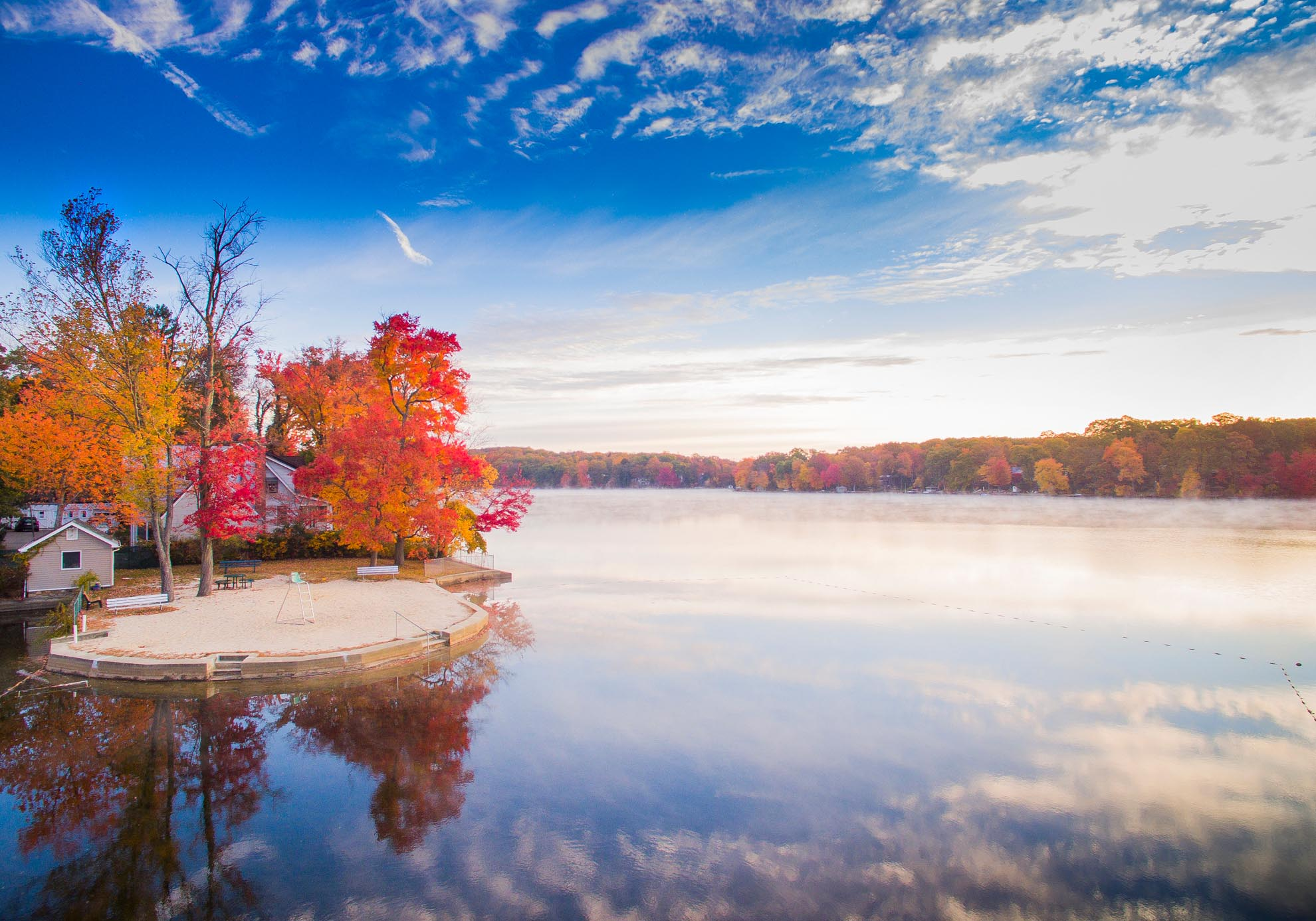 Photograph of Cedar Lake NJ in Autumn with morning fog taken from a drone
