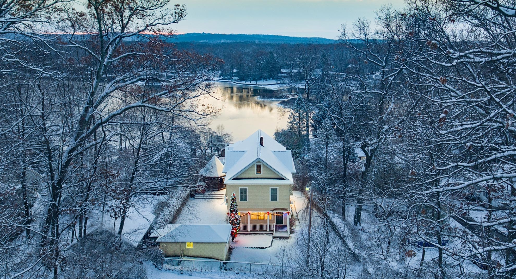 Drone Photograph of Lake Home with Christmas Decorations after snow fall