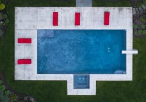Drone photograph of birds eye view of Blue swimming pool with red chairs