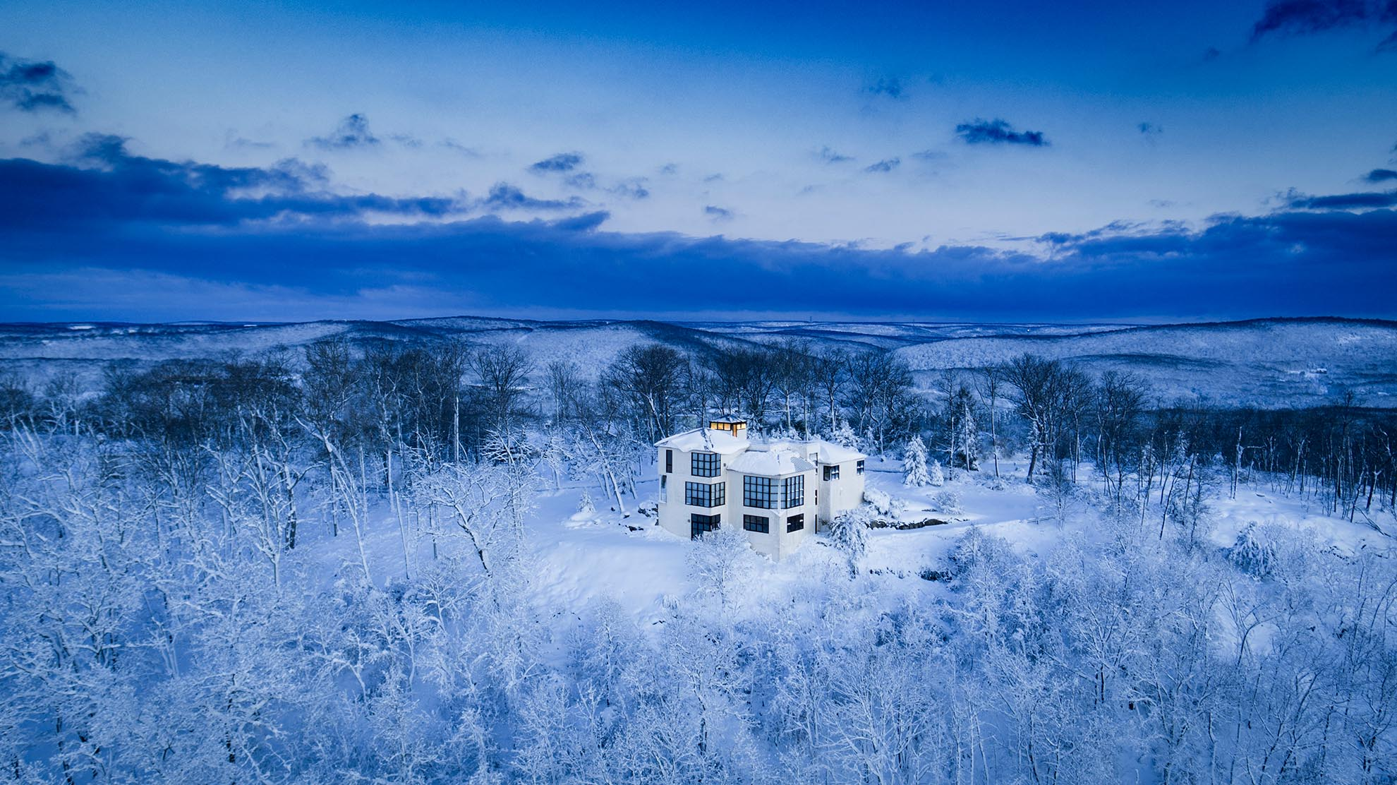 Drone Photograph of white Modern Home on Mountain Top after snow storm in NJ