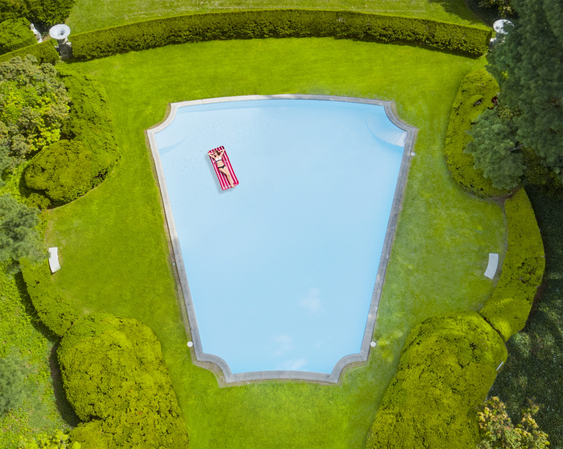 Drone Photograph of woman in a bikini lying on a float in a vintage swimming pool