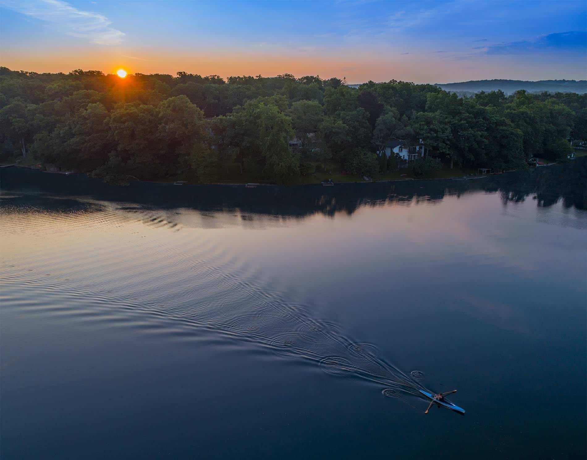 Drone Photograph of man rowing in a rowing scull at sunrise on Cedar Lake New Jersey