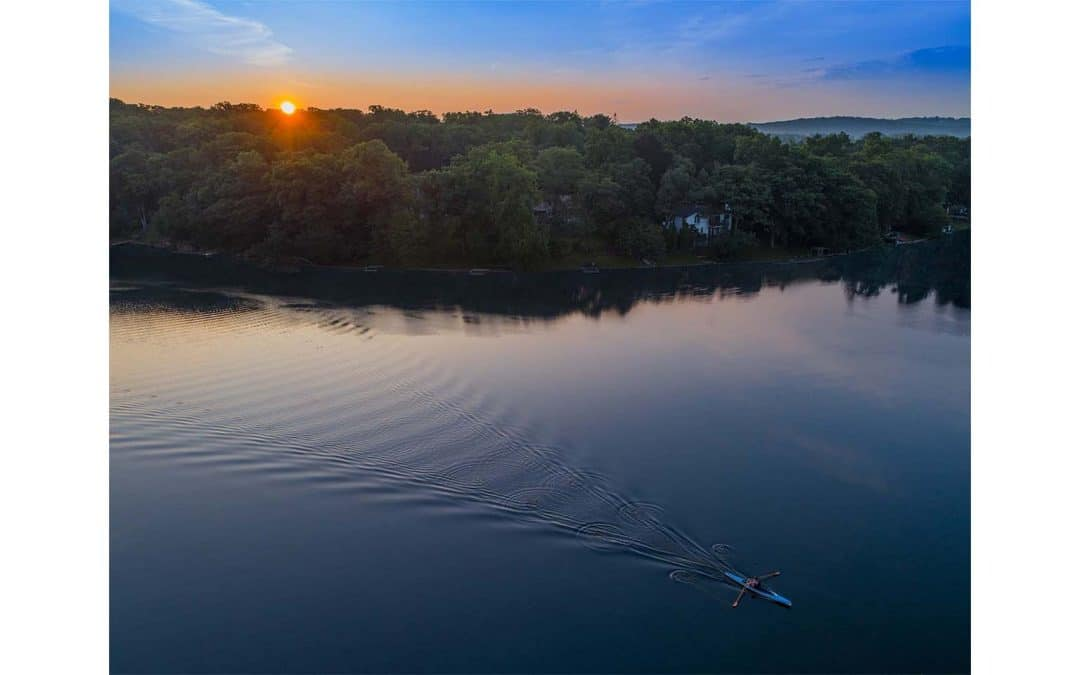 Drone photograph of a man in a single rowing scull during sunrise over Cedar Lake New Jersey