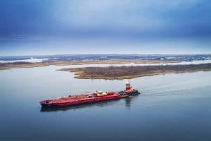 Drone Photograph of Red Barge being pushed by a Tug Boat going up the Arthur Kill River